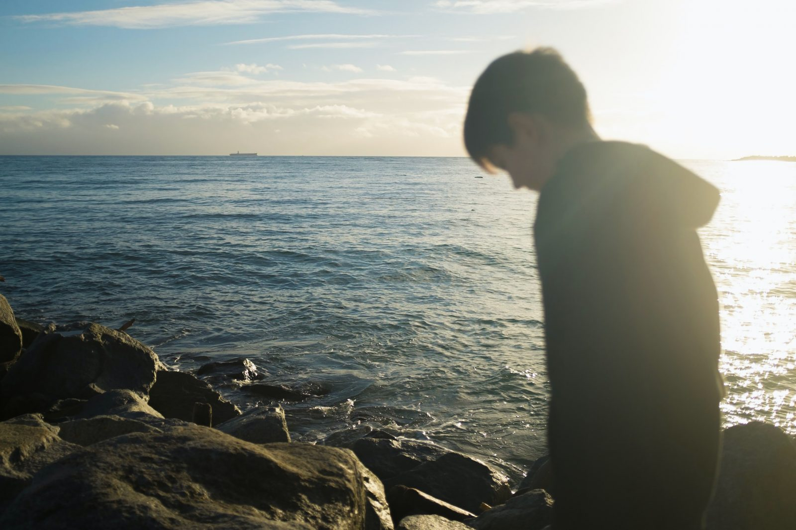 man standing on black rock formation during daytime